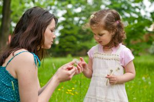 Mother speding time with small daughter  -playing with dandelions